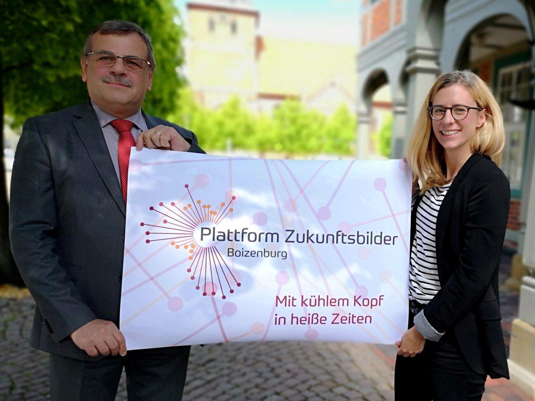 Boizenburgs Bürgermeister Harald Jäschke und Beatrice John zeigen das Plattform Zukunftsbilder Logo